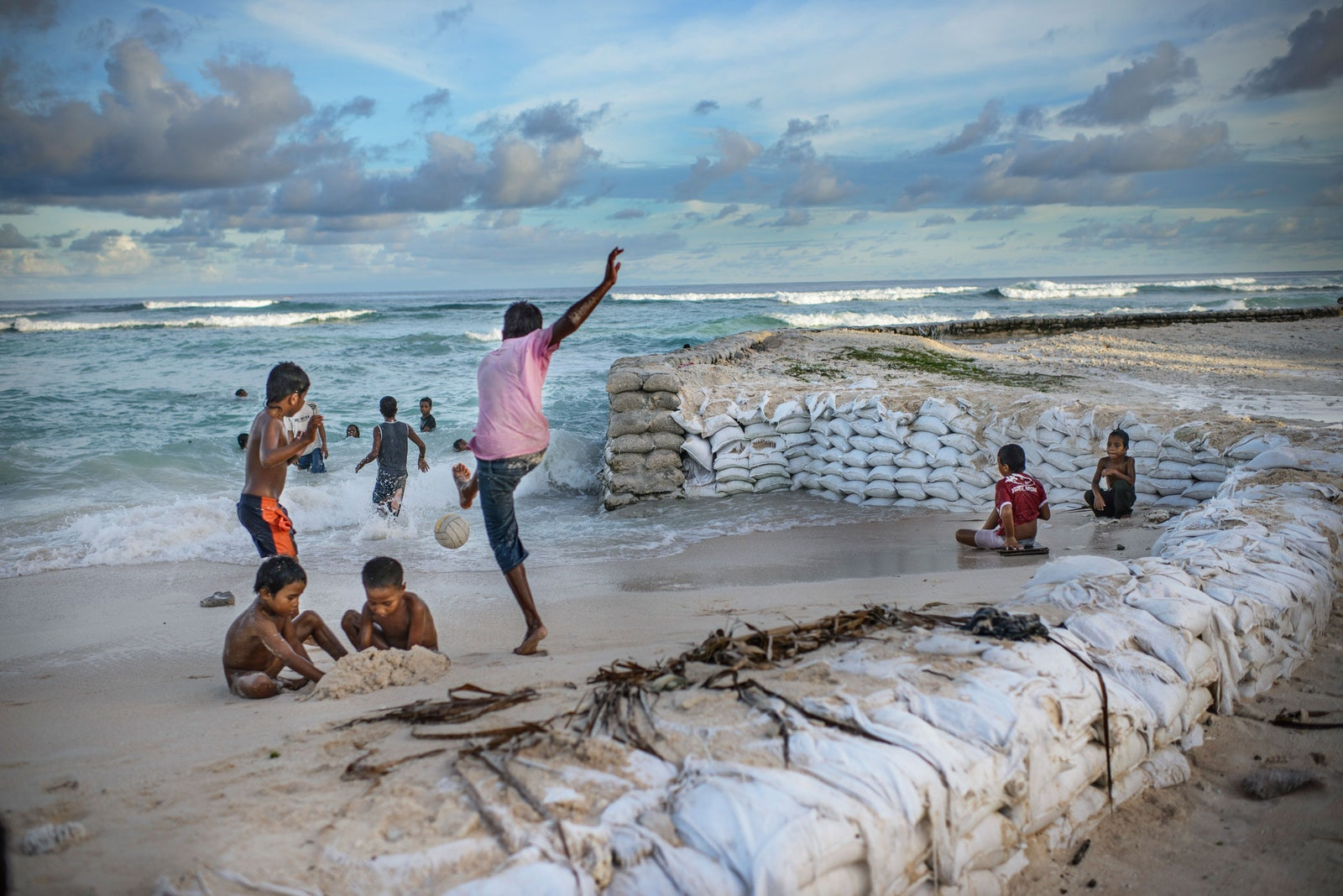niños jugando cerca de bolsas de arena.