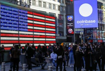 Employees of Coinbase Global Inc, the biggest U.S. cryptocurrency exchange, watch as their listing is displayed on the Nasdaq MarketSite jumbotron at Times Square in New York, U.S., April 14, 2021. REUTERS/Shannon Stapleton/File Photo