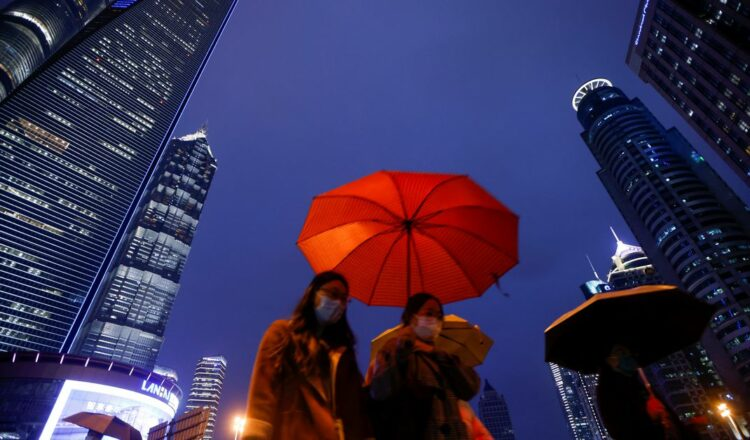 People walk with umbrellas in Lujiazui financial district in Pudong, Shanghai, on the day of the opening session of the National People