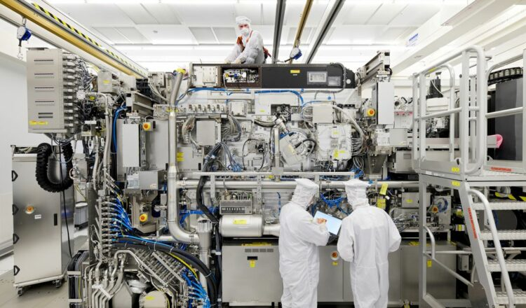 Employees are seen working on the final assembly of ASML