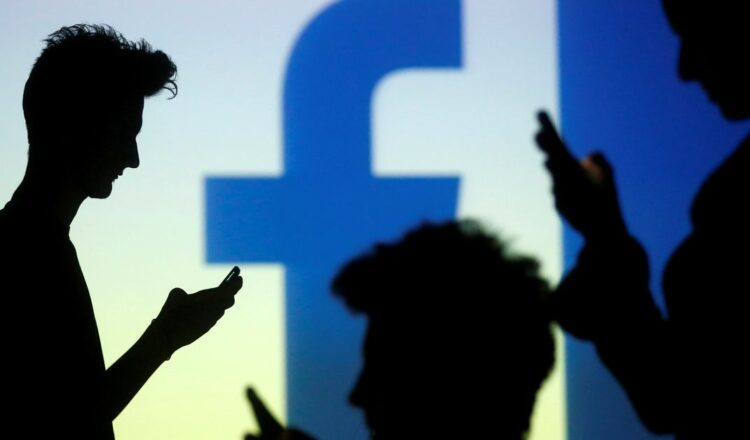 People are silhouetted as they pose with mobile devices in front of a screen projected with a Facebook logo, in this picture illustration taken in Zenica October 29, 2014. REUTERS/Dado Ruvic