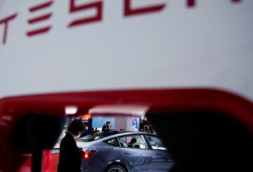 A Tesla electric vehicle (EV) is seen through a charging point displayed during a media day for the Auto Shanghai show in Shanghai, China April 20, 2021. REUTERS/Aly Song