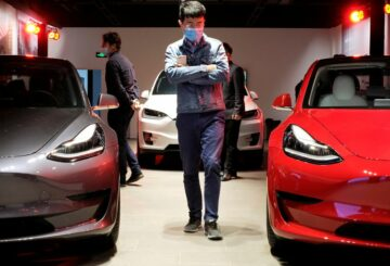 A man wearing a face mask following the coronavirus disease (COVID-19) outbreak walks by Tesla Model 3 sedans and Tesla Model X sport utility vehicle at a new Tesla showroom in Shanghai, China May 8, 2020. REUTERS/Yilei Sun