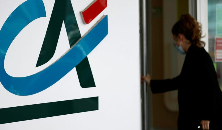 A woman walks past a Credit Agricole logo outside a bank office in Reze near Nantes, France, May 12, 2021. REUTERS/Stephane Mahe